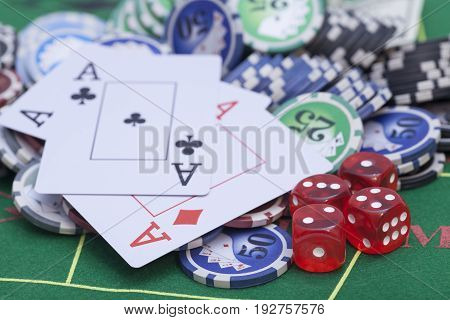 Casino chips cards and dices on green felt game table