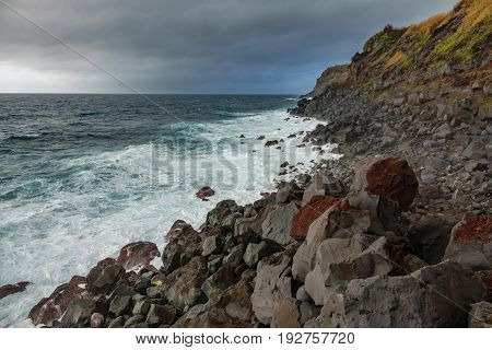 Wide angle view of volcanic rocks along coast, cloudy sky in Terceira, Portugal