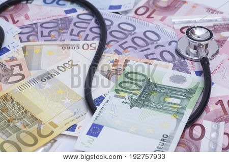 Euro banknotes and stethoscope close up .