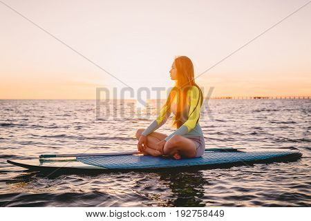 Stand up paddle boarding on a quiet sea with warm sunset colors. Young slim girl is relaxing on ocean