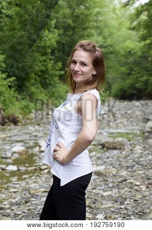 Blonde Girl On A Background Of A Mountain River And Forest. Posing Against The Backdrop Of The Mount