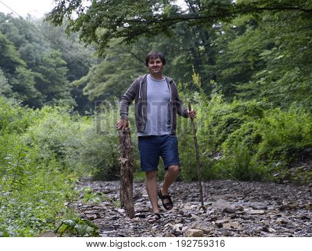 A man walks along the creek and carries wood for the fire. Picnic in nature. Harvesting of firewood.