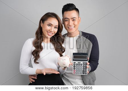 Young couple hold pink pig bank and calculator standing over on gray background