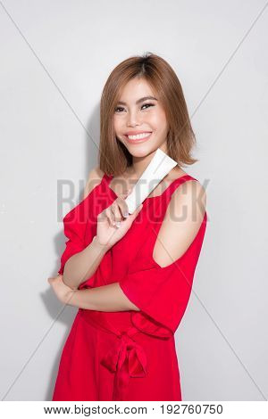 Beautiful asian woman standing red dress and holding cosmetic product.