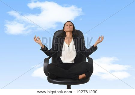 young beautiful latin american business woman sitting at office chair in lotus posture practicing yoga and meditation isolated as if floating or flying on blue sky background