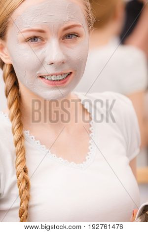 Happy Young Woman Having Mud Mask On Face