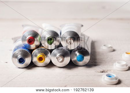 Open The Tubes Of Paint Of Different Colors On Wooden Background,