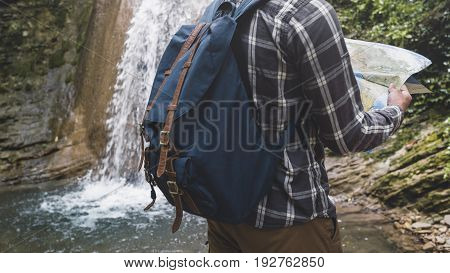 Traveler With A Backpack Is Standing By The Waterfall And Looks At The Map Holidays And Tourism Concept