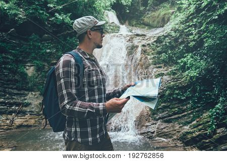 Hiker With Backpack Is Standing By Waterfall And Looks At The Map Holidays And Tourism Concept