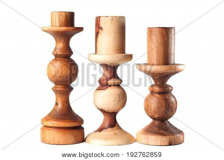 Three Wooden Candlesticks On A White Background,