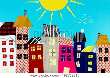 Fabric town. Houses the sun made of colorful pieces of fabric isolated on blue background.