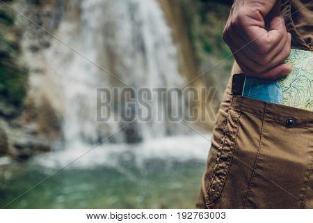 Unrecognizable Tourist Man Puts Map In Pocket Of Pants Hiking Travel Tourism Concept Selective Focus