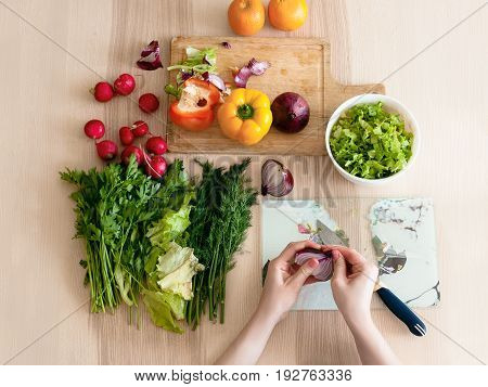 The girl sits in the kitchen and preparing a salad, cutting bow. Flat lay.