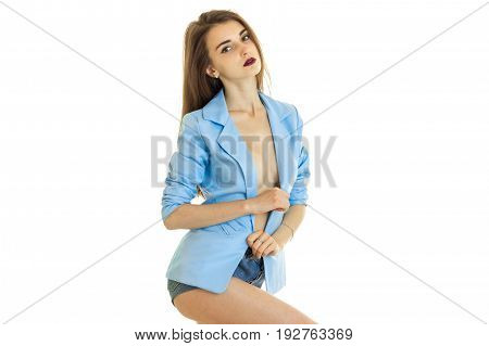 Slim sexy lady poses in the Studio in a blue jacket is isolated on a white background