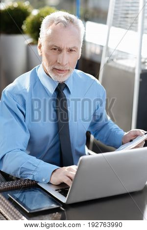 Use all devises. Handsome office worker wrinkling his forehead while touching laptop and doing special analysis