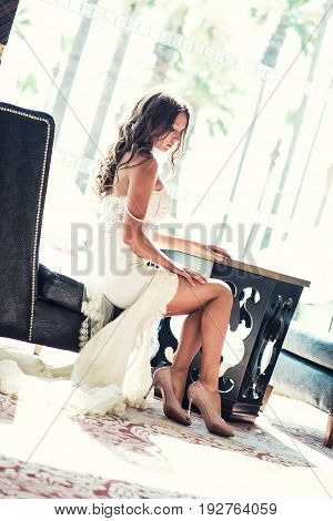 Charming bride in a beautiful wedding dress sitting in a chair near the window