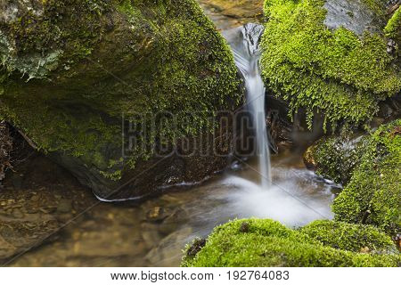 Detail shot of a small waterfall of the mountain creek Tro Maret in the Ardennes, Belgium.