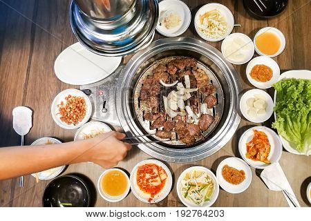 Person Barbecue Beef On Bbq Pit During Korean Meal Set