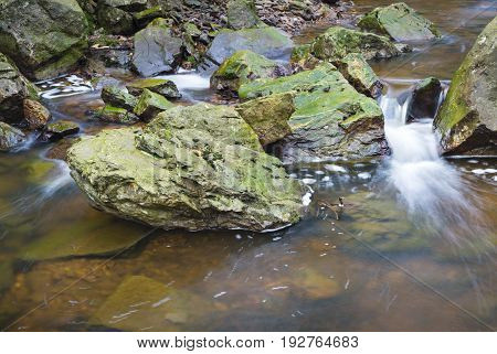 Tro Maret River in the Ardennes in East Belgium with brown  water running between green rocks forming bubbles.
