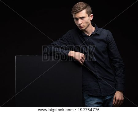 Young sexy man portrait of a confident businessman showing presentation, pointing paper placard black background. Ideal for banners, registration forms, presentation, landings, presenting concept.