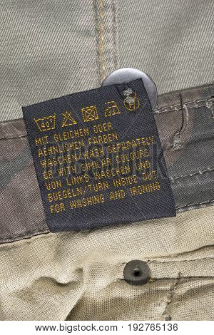 Washing instructions clothes label on khaki cloth as a background