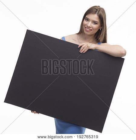 Young happy woman portrait of a confident businesswoman showing presentation, pointing paper placard black background. Ideal for banners, registration forms, presentation, landings, presenting concept.