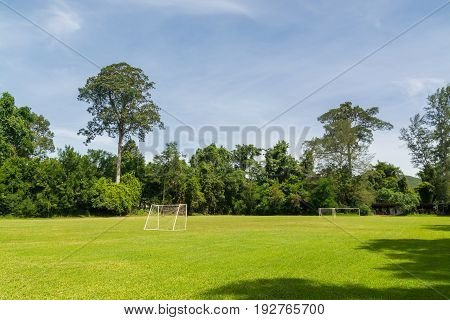Football or Soccer Field with Goal Pole in the Woods over Mountain of Thailand under Summer Day Blue Sky.