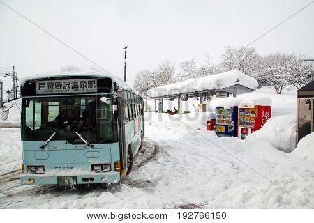Nozawa Onsen, Japan - December 26, 2014: A bus parking at a snowy train station