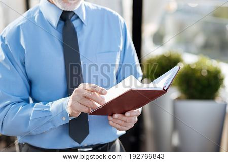 Turn next page. Grey haired man paging his notes and checking timetable while going to make new appointment