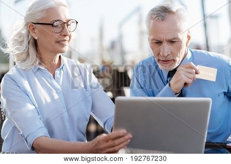 Have some doubts. Positive delighted woman keeping smile on her face and sitting in semi position while holding laptop in right hand