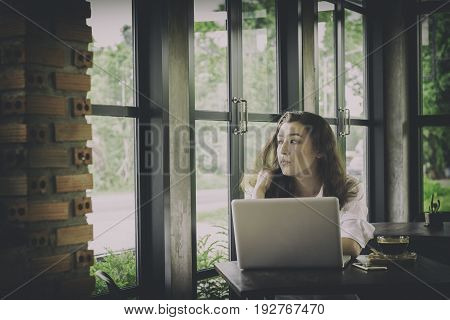 Young woman sitting at desk working with laptop computer at home serious thinking.vintage style with vignette effect.