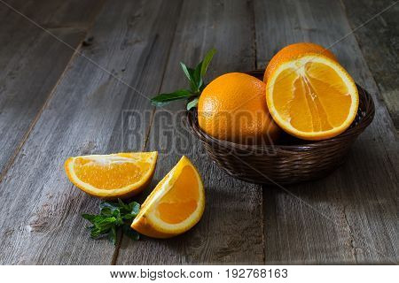 Whole and cut oranges with mint leaves close-up in a wicker basket on a wooden background. Rustic style