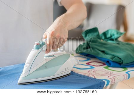 Iron On An Ironing Board With A Blue Shirt Close Up From The Side With A Stack Of Laundry