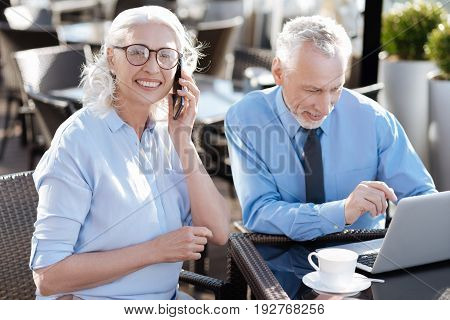 Feeling good. Positive grey haired man bowing his head while watching video on his laptop and leaning elbows on the table