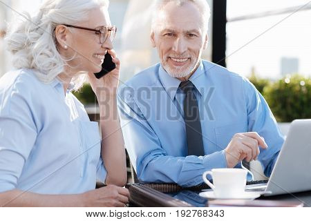 She is my colleague. Delighted blonde keeping smile on her face and holding telephone near left ear while sitting in semi position