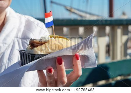 Woman holding traditional Dutch snack with raw herring in plastic container