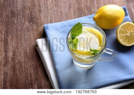 Cup of cold lemon water and napkins on wooden table