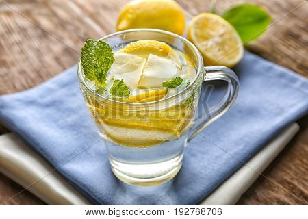 Cup of cold lemon water and napkins on wooden table, closeup