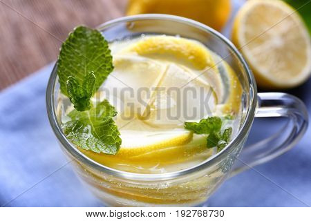 Cup of cold lemon water on table, closeup