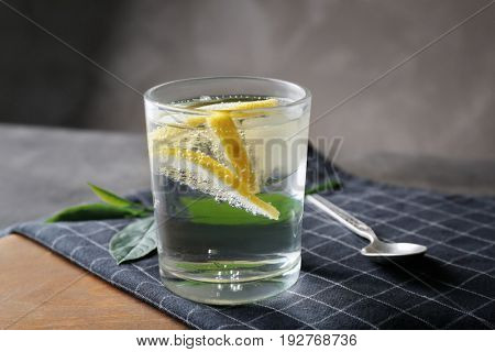Glass of cold lemon water, spoon and napkin on table, closeup