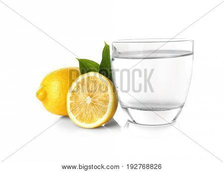 Glass of water and fresh lemons on white background