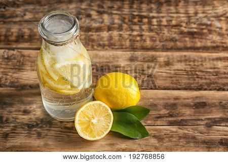 Bottle with cold lemon water on wooden table