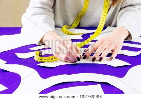 Workplace of a dressmaker. Girl drawing a pattern for the dress with a chalk.