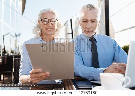 Answer my questions. Positive delighted blonde holding documents in right hand while reading them and showing to her partner