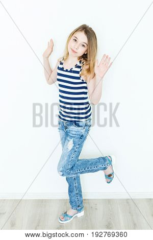 Jumping cute girl eleven years old with blond long hair standing near white wall and upwards hands