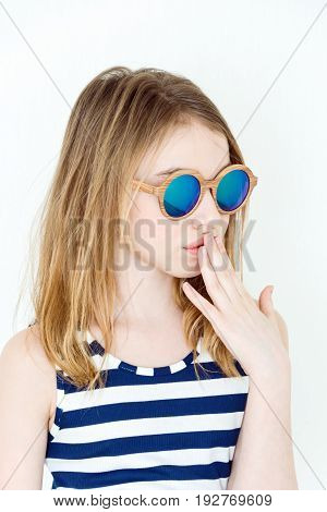 Cute girl eleven years old in green sunglass on white