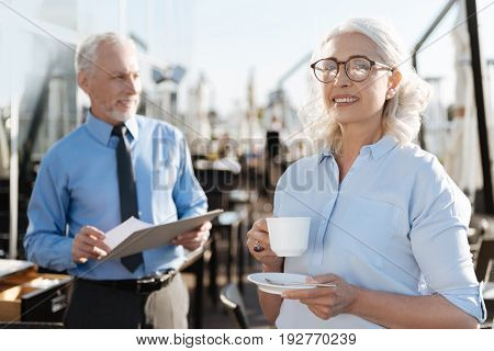 Look in future. Positive smiling female person holding cup with tea while going to drink it and standing on the foreground