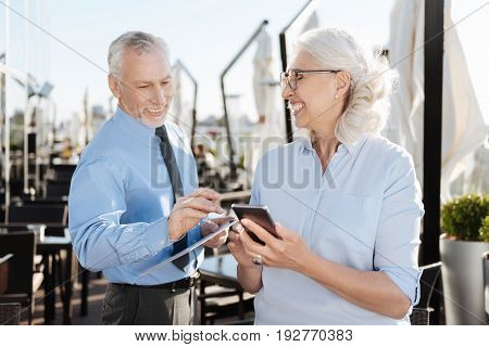 Let me read it. Smiling woman holding telephone in left hand and standing in semi position while feeling happiness