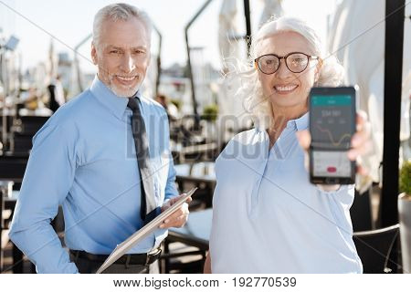 Important news. Positive delighted man standing near his colleague and holding folder in both hands while looking straight at camera