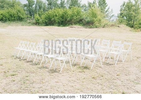 Many rows of white wooden chairs for a wedding ceremony in nature